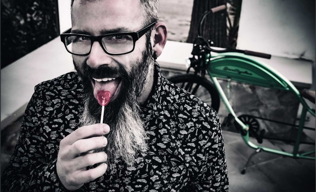 hombre con barba sacando la lengua con piruleta