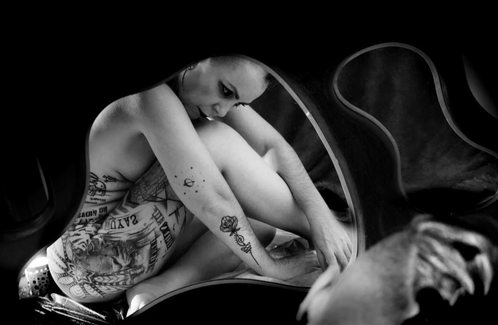 retrato mujer desnuda tatuada frente espejo