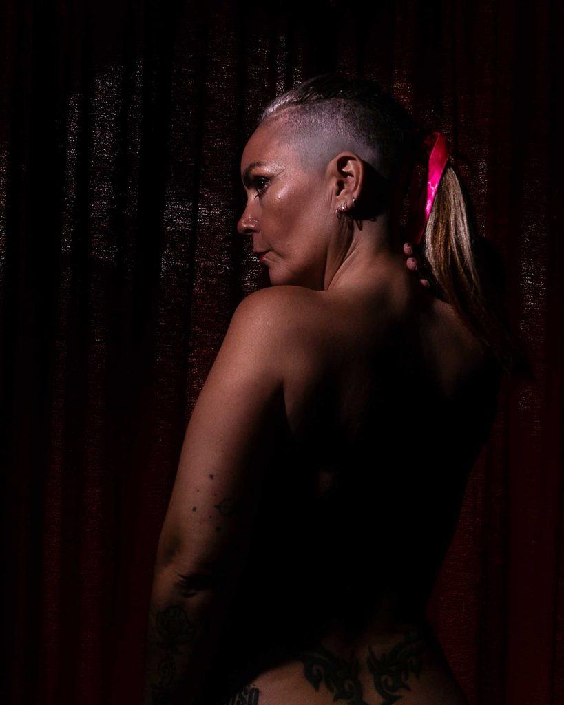 retrato mujer rapada con trenza y lazo fucsia
