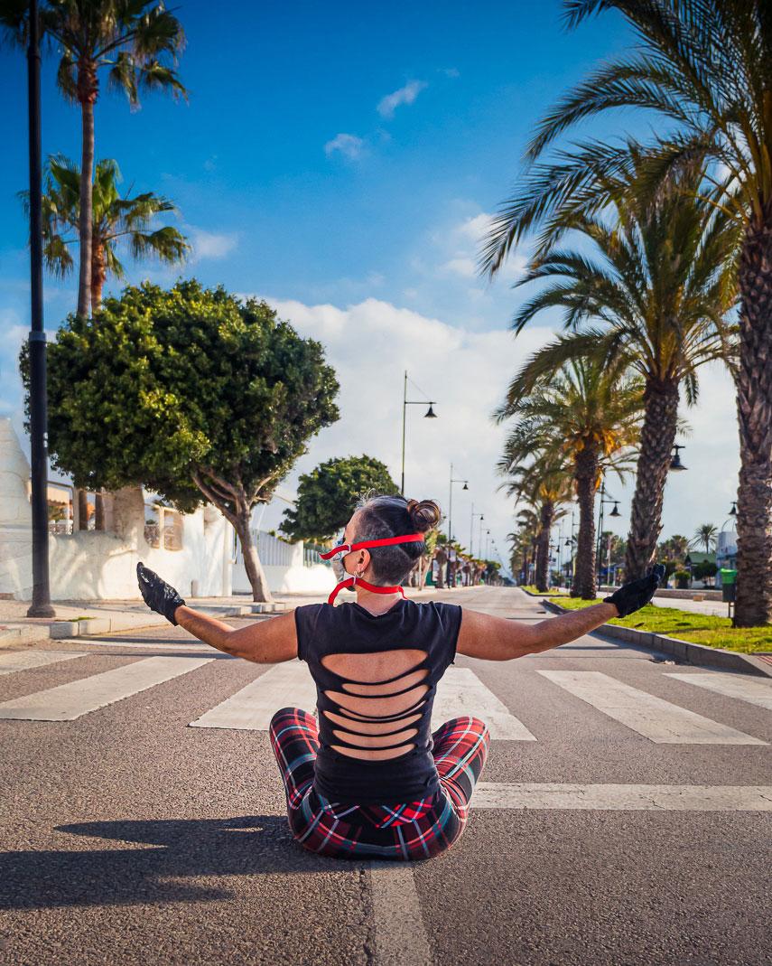 mujer sentada en carretera de espaldas paseo marítimo
