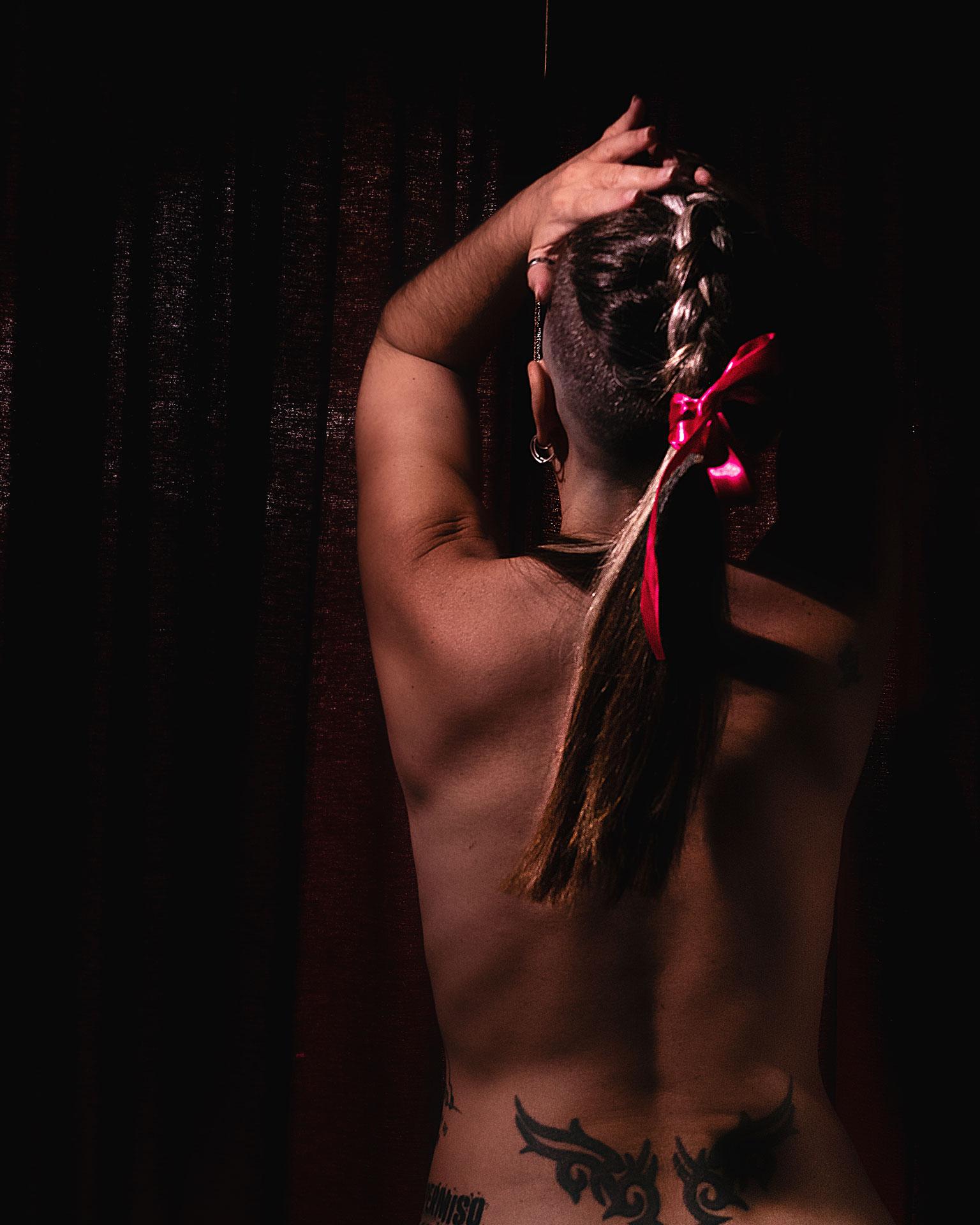 mujer espalda desnuda trenza y lazo fucsia