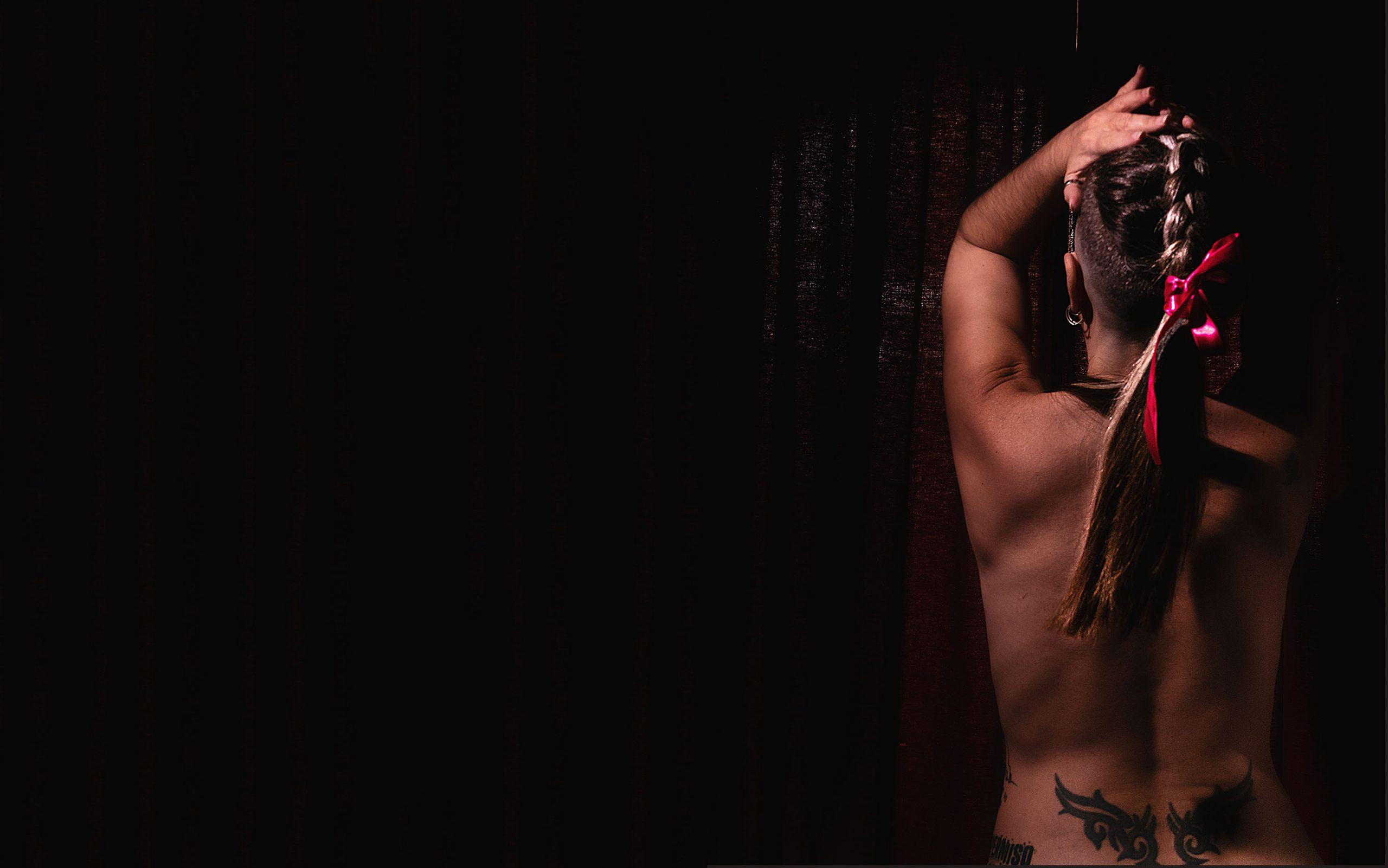 mujer de espaldas desnuda y trenza en el pelo