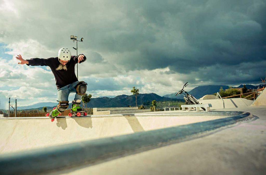Patinador quad en rampa skatepark Pizarra nubes de fondo