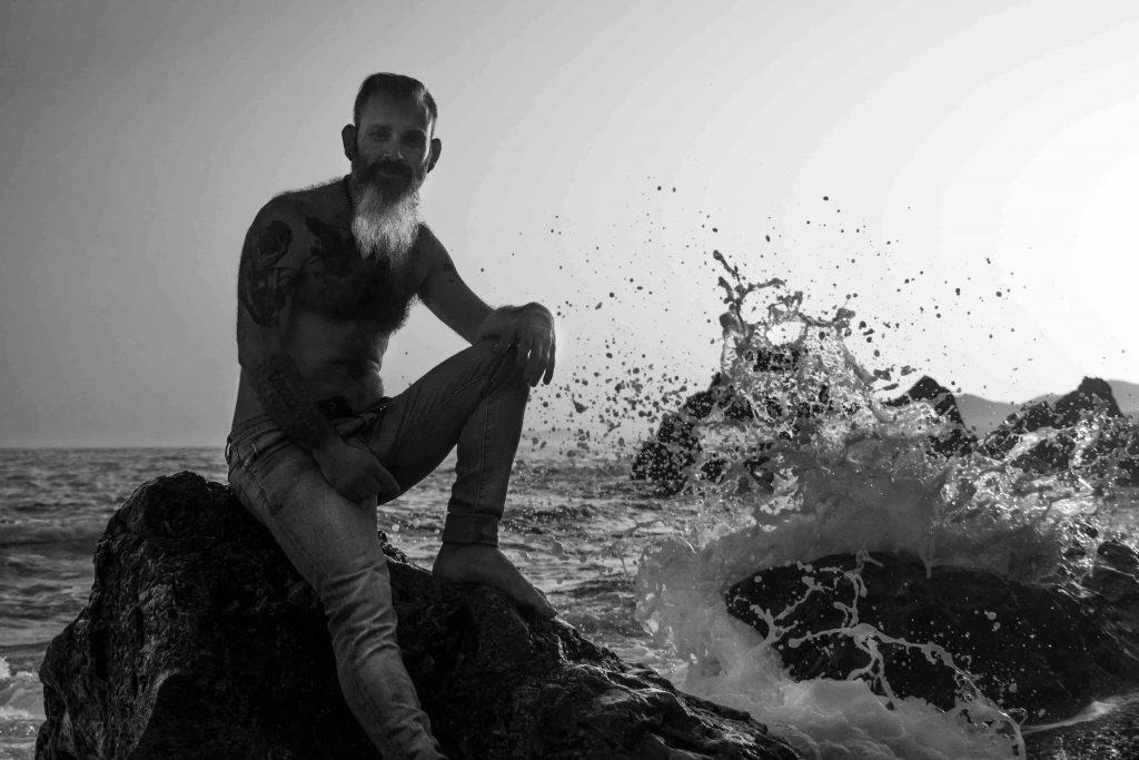 retrato hombre con barba y tatuajes en la playa de rocas al atardecer en Maro, Málaga