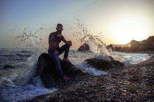retrato hombre con barba y tatuajes en la playa de rocas al atardecer en Maro, Málaga agua golpeando las rocas