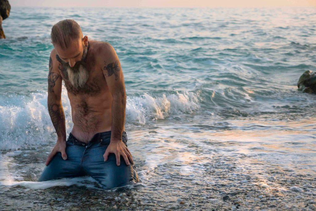 retrato hombre con barba y tatuajes en la playa de rocas al atardecer en Maro, Málaga arrodillado