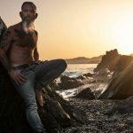 retrato hombre con barba y tatuajes en la playa de rocas al atardecer en Maro
