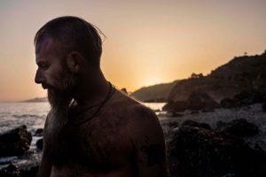 retrato hombre con barba y tatuajes en la playa de rocas al atardecer