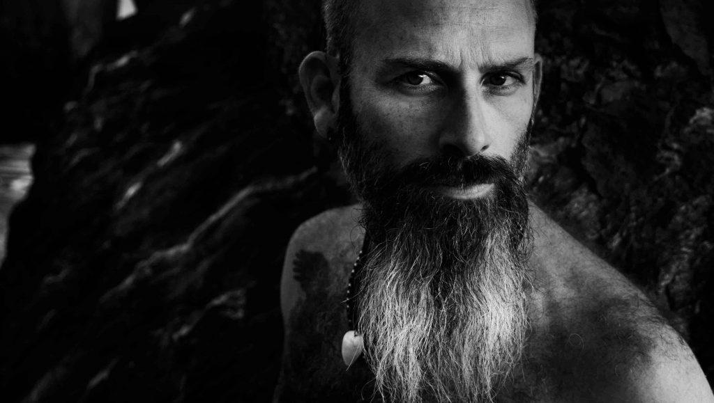 retrato hombre con barba en la playa de rocas