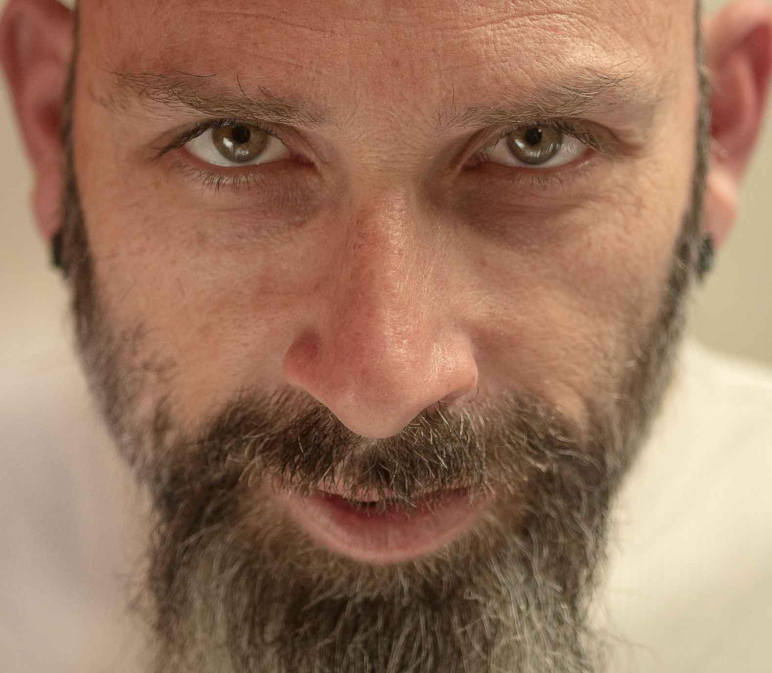 retrato primer plano hombre ojos verdes simula Hannibal Lecter
