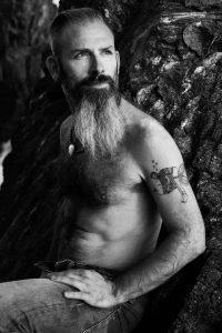 retrato hombre con barba y tatuajes en la playa de rocas