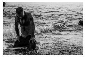 hombre arrodillado en la orilla