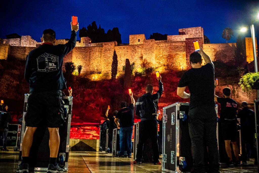 Alcazaba de Málaga y trabajadores frente a ella protestando alerta roja