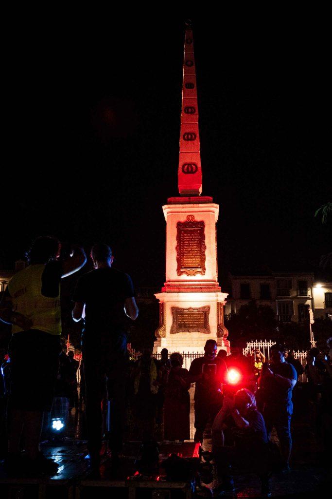 Plaza de Merced Málaga de noche iluminación roja. Protesta alerta roja